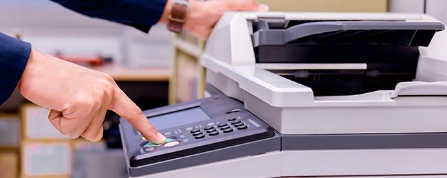 mano de hombre de negocios presionando el boton de la impresora